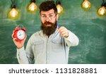 bearded hipster holds clock ... | Shutterstock . vector #1131828881
