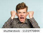 Small photo of emotional breakdown. angry enraged infuriated crazy man screaming. portrait of a young guy on light background. emotion facial expression. feelings and people reaction.