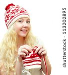 smiling woman in winter cap knitting winter patterns - stock photo