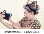 Woman holding a vintage 4x6 film camera on wallpaper.
