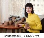 Female gardener with various seedlings at home - stock photo
