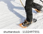 Small photo of Man with orange snowshoe on the snow path. Man in snowshoes with trekking poles is the snow in the mountains. Snowshoe is most versatile and highest-performing backcountry shoe