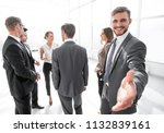 smiling businessman gives hand... | Shutterstock . vector #1132839161
