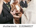 priest putting on wedding rings ... | Shutterstock . vector #1132868327
