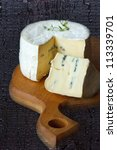 Wheel of blue cheese on a wooden board. - stock photo