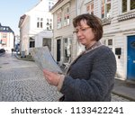 middle aged woman looks at a... | Shutterstock . vector #1133422241