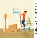 woman hanging picture on the... | Shutterstock .eps vector #1133520434