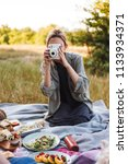 Pretty girl sitting on picnic blanket on grass covering face with white polaroid camera spending time in park