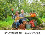 Happy parents and child with  harvested vegetables in garden - stock photo