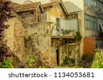 Small photo of Landscape of ruined buildings at sunset, image of decrepitude or natural disaster