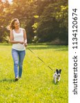 Stock photo beautiful woman enjoys walking with her cute dog jack russell terrier in the nature image is 1134120674