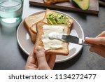 woman spreading butter on... | Shutterstock . vector #1134272477