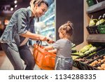 mom and daughter are shopping... | Shutterstock . vector #1134288335