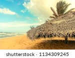 sunshade of palm leaves on a... | Shutterstock . vector #1134309245
