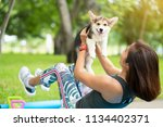 Stock photo a healthy woman playing with a corgi puppy while excersing on yoga mat surrounding with gym tools 1134402371