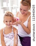 Beauty ritual - little girl and mother applying body lotion after bath - stock photo