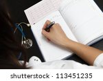 Doctor writing medical records - stock photo