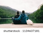 couple with dog sitting on dock ... | Shutterstock . vector #1134637181