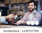 man working in a coffee shop... | Shutterstock . vector #1134717704
