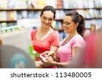 two young woman choosing a book ... | Shutterstock . vector #113480005