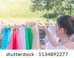 Stock photo young woman are putting white laundry on a rope with plastic colorful clothespins to dry 1134892277