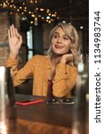 Small photo of Hey there. Tipsy young woman sitting at the bar counter and waving at someone, having noticed them