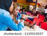 woman showing her friend... | Shutterstock . vector #1135015037