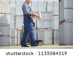 cargo mover in checkered shirt... | Shutterstock . vector #1135084319
