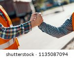 close up of two workers shaking ... | Shutterstock . vector #1135087094