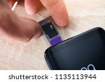 man inserting memory card and... | Shutterstock . vector #1135113944