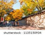 Small photo of Seoul, Korea - November 9, 2016 : Deoksugung stonewall walkway with autumn maple