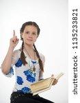 young pretty schoolgirl sitting ... | Shutterstock . vector #1135233821