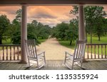 Rocking chairs on southern porch looking down oak lined road