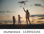 happy family on the field.... | Shutterstock . vector #1135412141