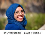 Small photo of Portrait of a young adult muslim algerian beautiful woman wearing a blue hijab and glasses smiling and looking to camera