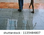 man and woman walking along wet ... | Shutterstock . vector #1135484807
