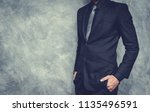 man in suit on a concrete wall... | Shutterstock . vector #1135496591