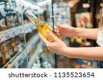 female buyer choosing a beer in ... | Shutterstock . vector #1135523654
