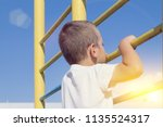 a blond boy holds onto the... | Shutterstock . vector #1135524317