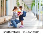 first day at school. mother... | Shutterstock . vector #1135645004