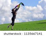a woman wants to fly a kite in... | Shutterstock . vector #1135667141