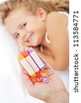 Homeopathic medication in woman hand - little smiling girl in background - stock photo