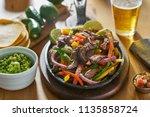 mexican beef fajitas in iron... | Shutterstock . vector #1135858724