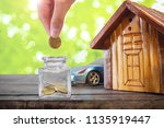 hand putting golden coins in... | Shutterstock . vector #1135919447