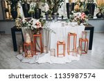 in banquet hall next to table... | Shutterstock . vector #1135987574