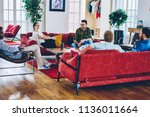 Group of smiling multiracial people resting at modern apartments with comfortable design furniture in house, diversity group of male and female friends talking and having fun on common leisure