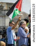 London, United Kingdom, 13th July 2018: An unknown protester waves the flag of the State of Palestine at an anti Trump rally in Central London - stock photo