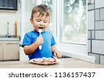 hungry baby eating dumplings in ... | Shutterstock . vector #1136157437