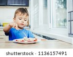 hungry baby eating dumplings in ... | Shutterstock . vector #1136157491