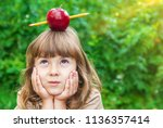 Small photo of little girl student with a red apple. Selective focus. nature.
